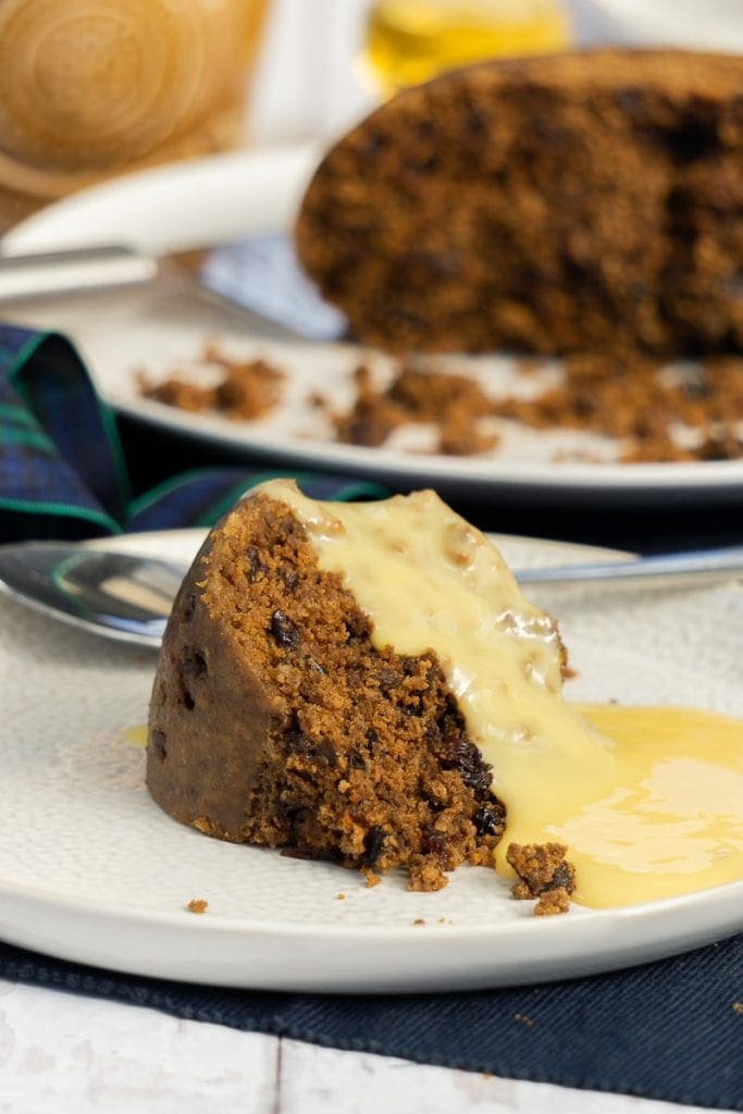 Scottish Clootie Dumpling Recipe on a plate with custard and whole pudding in the background