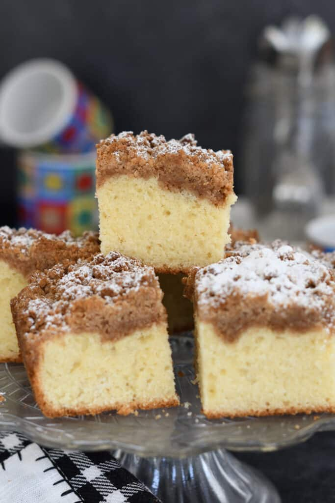 a stack of sourdough discard crumb cake slices on a cake stand