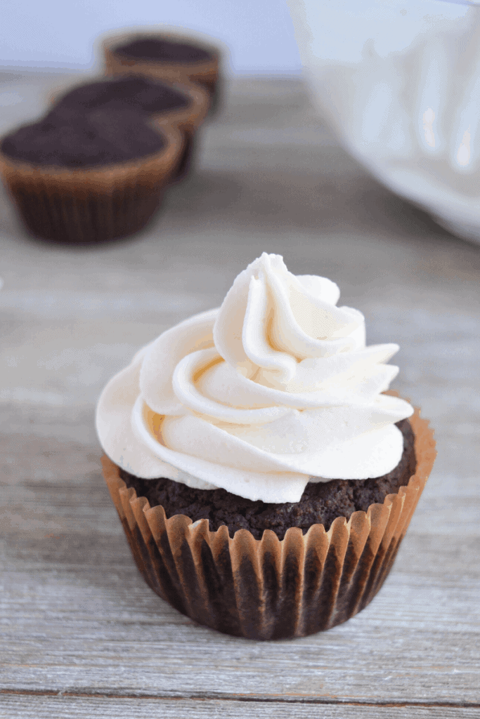 one frosted cupcake is in the foreground and 3 unfrosted cupcakes are blurred in the background