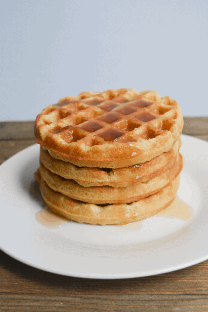 stack of keto waffles on a white plate drizzled in syrup