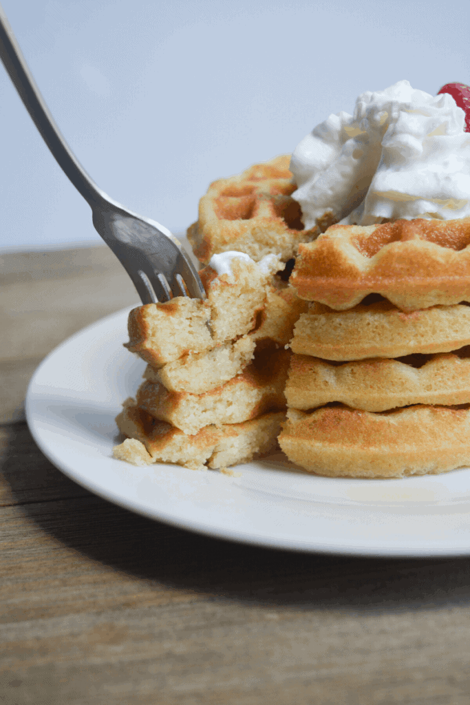 stack of keto waffles on a white plate with whipped cream and a strawberry on top