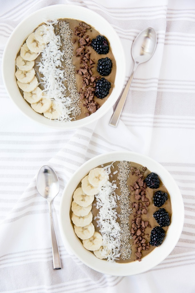 chocolate smoothie bowls topped with fruit, coconut, and chocolate