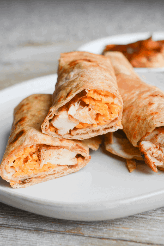 three tortillas wrapped around bbq chicken, ranch dressing and cheddar cheese