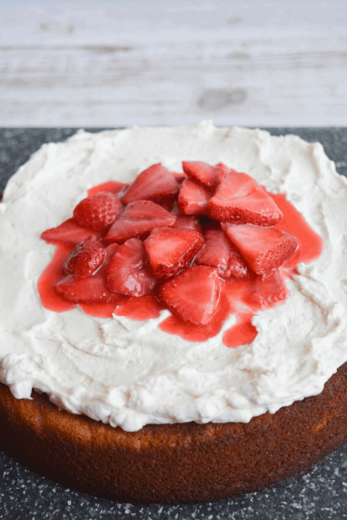 full strawberry cake with whipped cream frosting and fresh strawberries