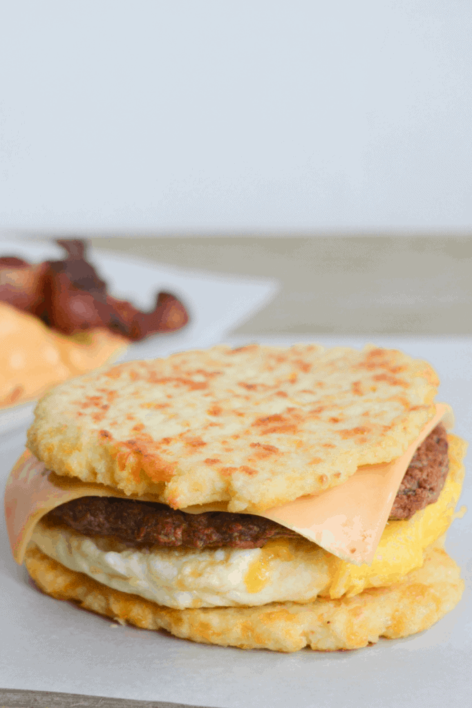 egg, sausage patty, and cheese sandwiched between two cauliflower buns