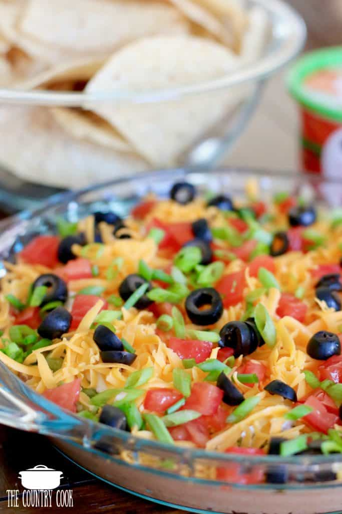 7 Layer Dip with beans, guacamole, ranch dip, cheese, tomatoes, green onions and olives