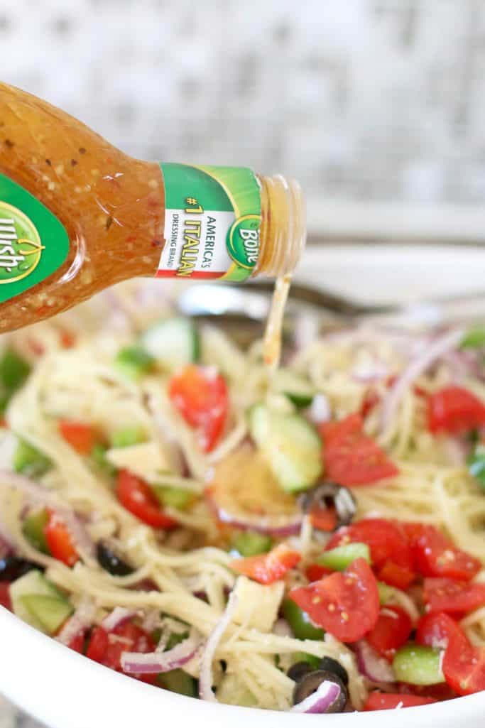 wish Bone Zest Italian Dressing poured over prepared spaghetti noodle salad