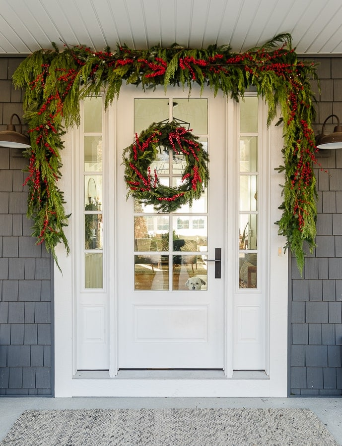 Front porch decorated for Christmas with cedar garland and red winter berries.