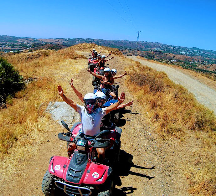 a group of quad bike riders in a row happy holding hands up in delight