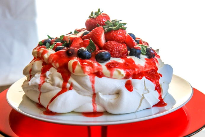Pavlova recipe with whipped cream, strawberries and raspberry coulis