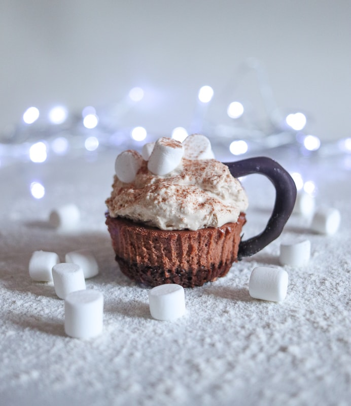 Hot chocolate mini cheesecake recipe. These cheesecake bites look like cups of hot chocolate topped with marshmallow and dusted with chocolate.