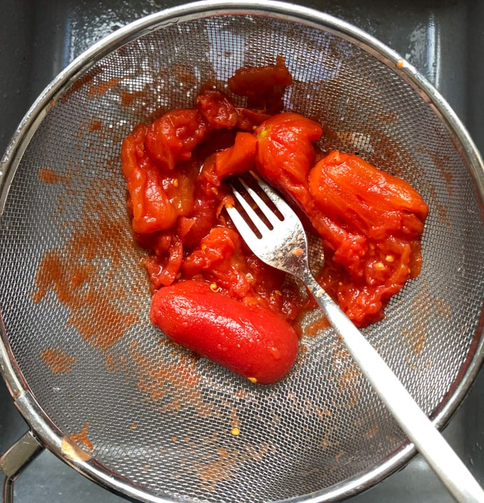 Bright red tinned tomatoes in a sieve