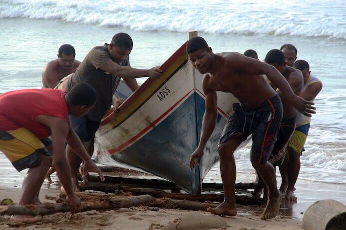 fishermen pulling their oat on a beach in Venezuela