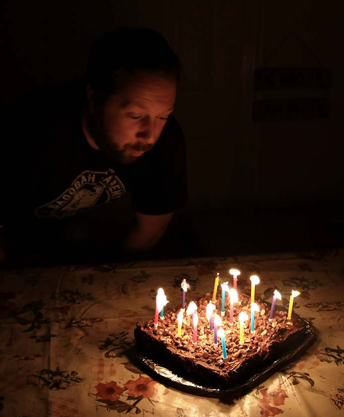 A man blowing out the birthday candles on the salted caramel chocolate cake with chocolate frosting and pecan and walnuts. Salted Caramel Chocolate Cake Recipe