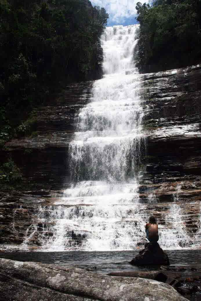 a man looking very small beside a large waterfall in Venezuela