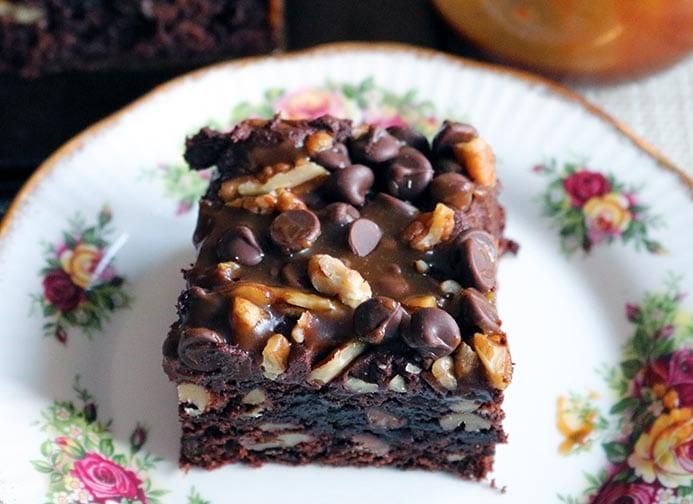 A slice of salted caramel chocolate cake with chocolate frosting and pecan and walnuts.