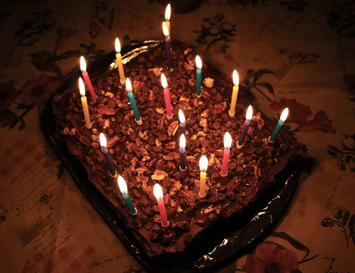 Lit birthday candles on top of the salted caramel chocolate cake with chocolate frosting topped with nuts and more caramel