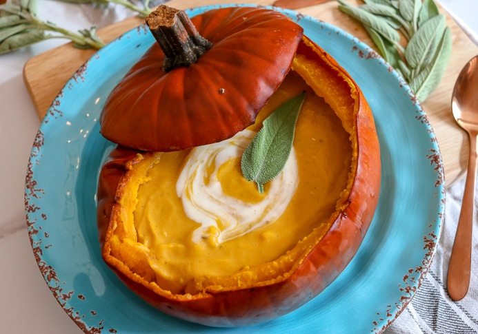Pumpkin Soup Recipe served in a pumpkin shell garnished with cream and herbs.