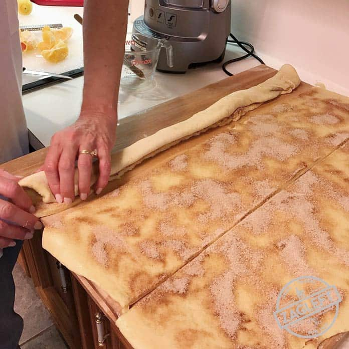 Rolling the three strips of dough topped with cinnamon sugar