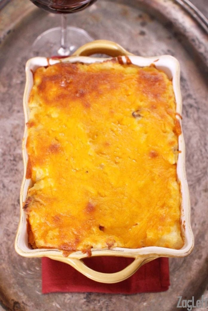 Twice Baked Potato Casserole in a baking dish on a metal tray with a glass of red wine