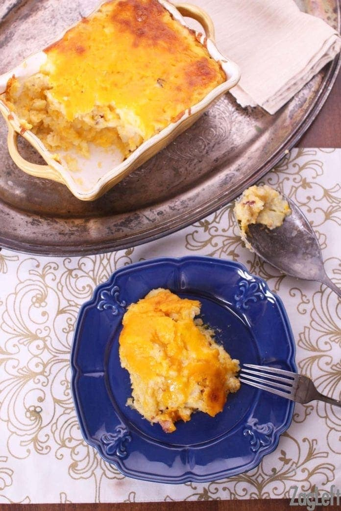 A slice of Twice Baked Potato Casserole on a small blue plate with a fork next to a metal tray holding the casserole in a baking dish