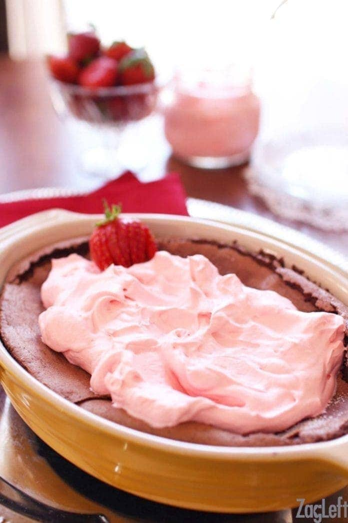Gluten Free Chocolate Cake topped with strawberry whipped cream in a baking dish