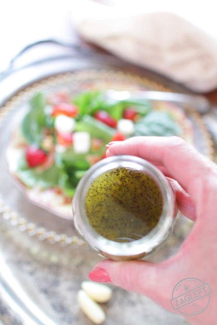 Overhead view of a jar of Poppy Seed Salad Dressing being held over a spinach salad