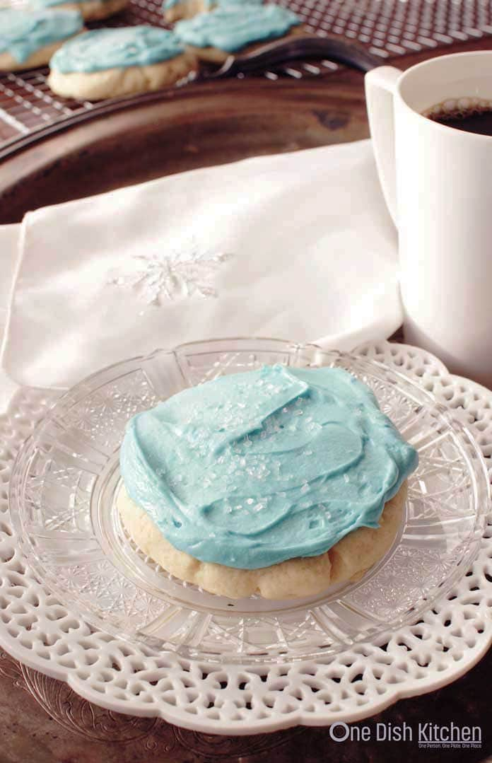 A blue frosted sugar cookie with white crystal sprinkles on a plate next to a mug of coffee and cookies on a cooling rack in the background