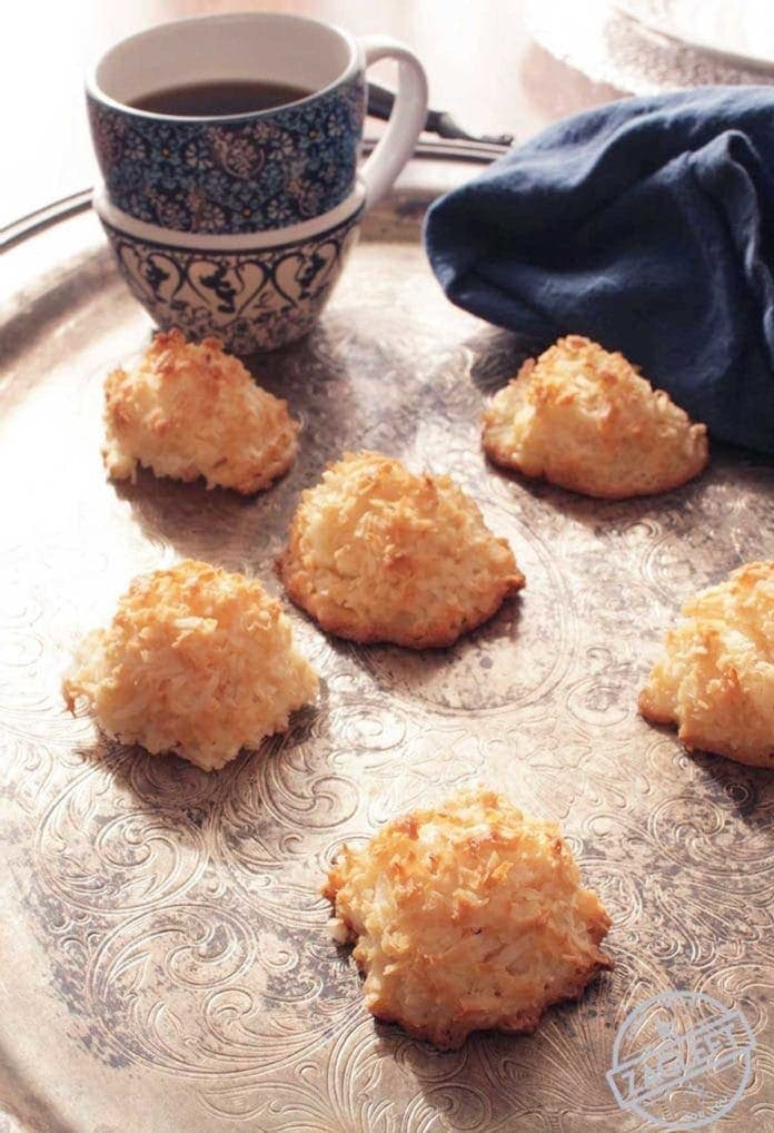 Six coconut macaroons spread out on a metal tray with a navy blue napkin and a coffee mug