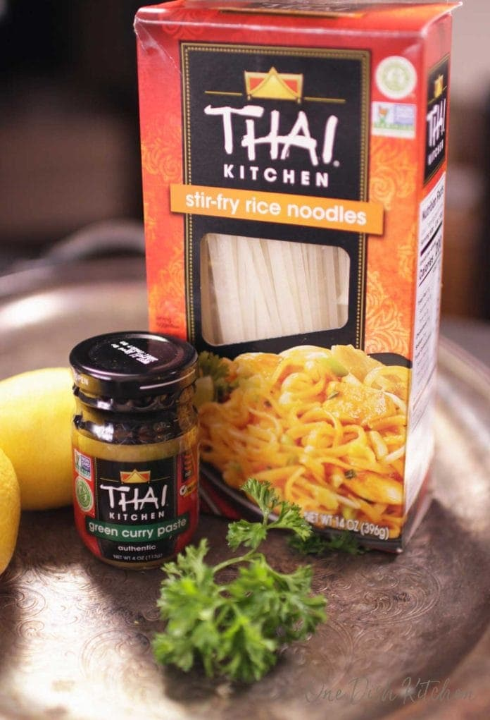 A small jar of Thai green curry paste and a box of rice noodles all on a metal tray