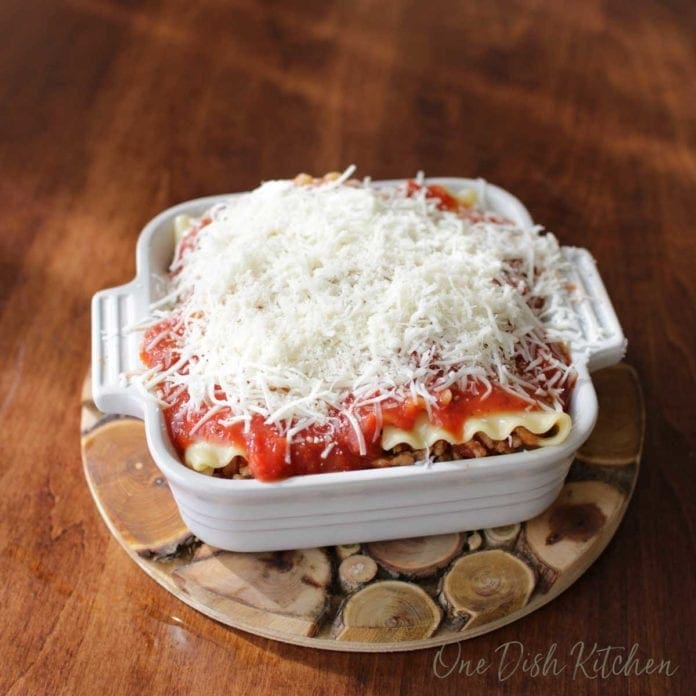 a lasagna covered with shredded mozzarella cheese before baking in the oven | one dish kitchen