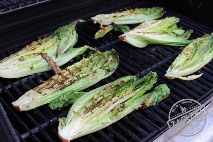 Romaine lettuce on the grill with char marks after it has been turned
