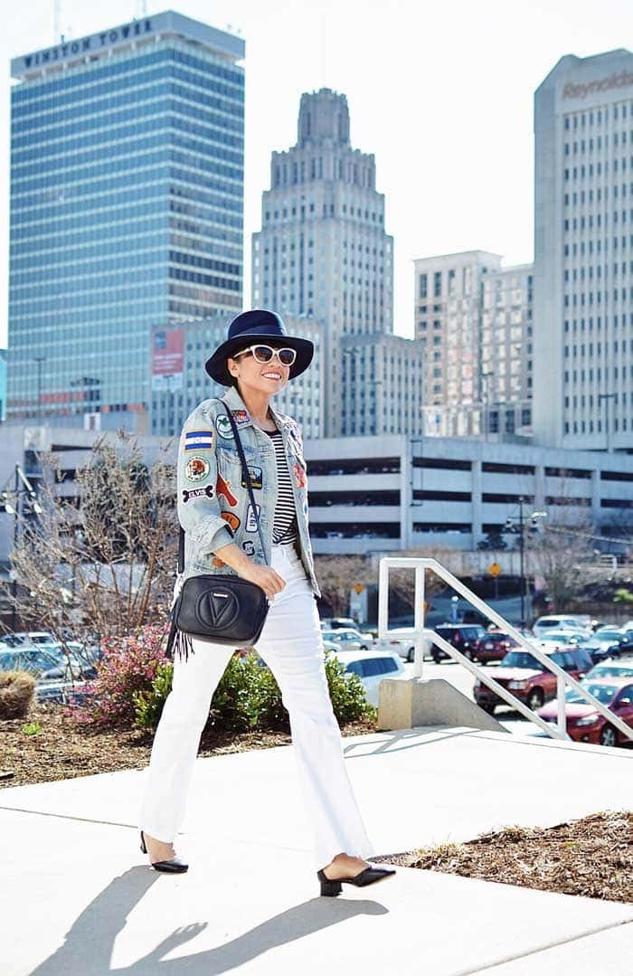 Carelia wearing patched denim jacket and white pants | 40plusstyle.com