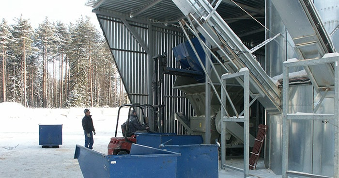 Wood being loaded into wood shredded with conveyor