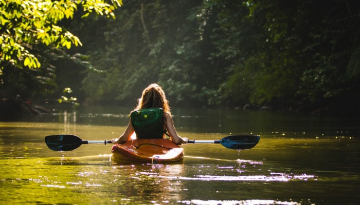 Person using a dry bag backpack on a kayak