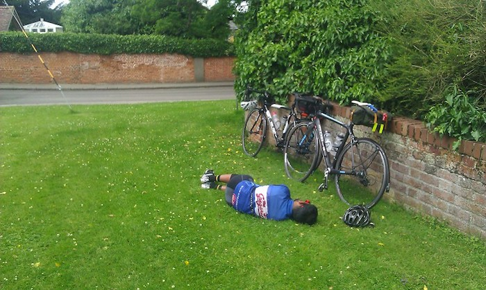 Cyclist taking a nap in the grass beside his bike