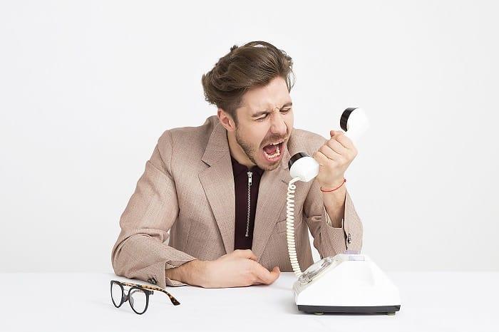 man shouting down telephone