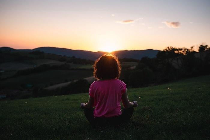 woman meditating at sunset