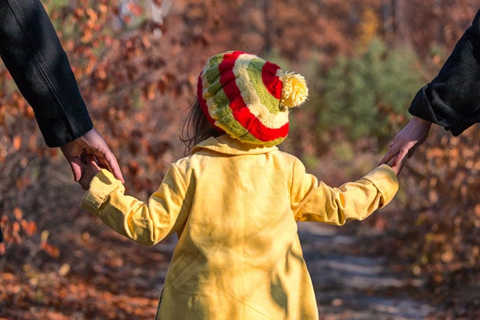 Parents holding the hands of a child, who is always put first in the collaborative law process, created to give people who need a divorce lawyer a low cost way to obtain a no contest divorce, an uncontested divorce or out of court divorce in Alberta.