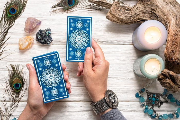 person reading tarot with crystals