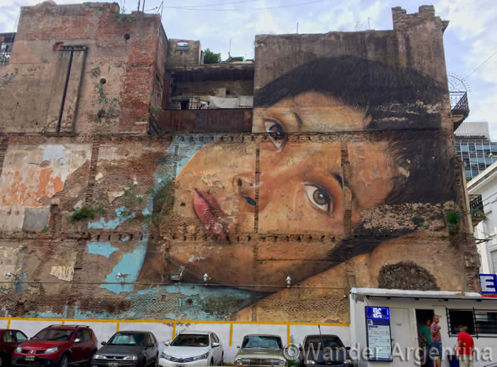 Large scale realist graffiti of a boy's face in Buenos Aires