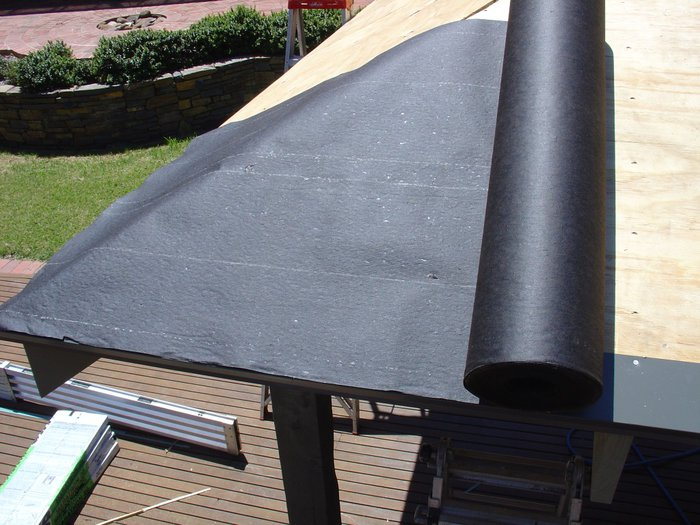 Rolling out the asphalt saturated felt paper in line with the drip edge