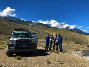 3 people posing for a photo in front of a jeep in Upper Mustang