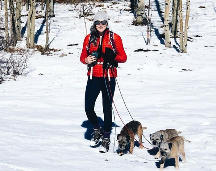 Amanda wears a bright red coat for a walk with her three dogs   40plusstyle.com
