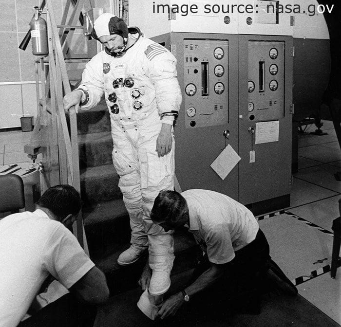 Ассистенты Nasa надевают на командира Neil Armstrong лунные ботинки