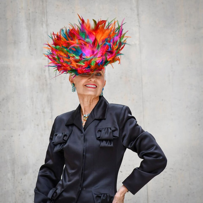 Judith in black silk outfit with colorful feathered hat | 40plusstyle.com