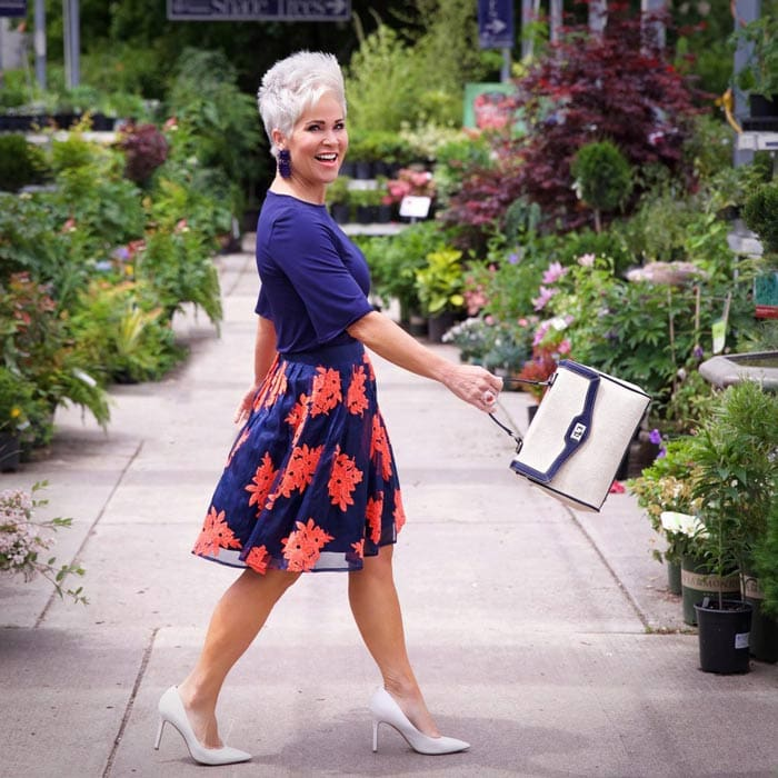 Shauna wearing navy top and floral skirt | 40plusstyle.com