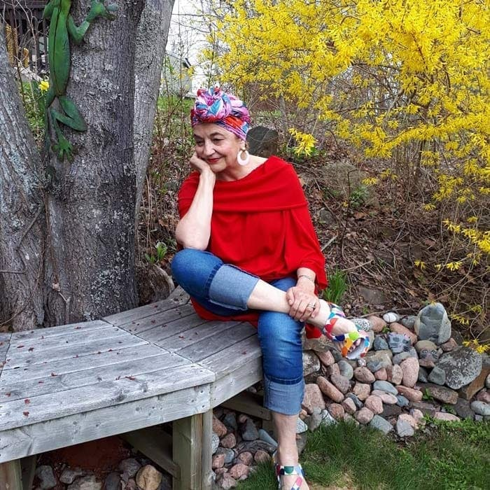Terrie wearing a red top, jeans with head wrap | 40plusstyle.com