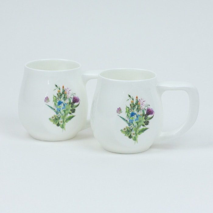 A pair of white fine bone china mugs with a colourful butterfly printed on the side.