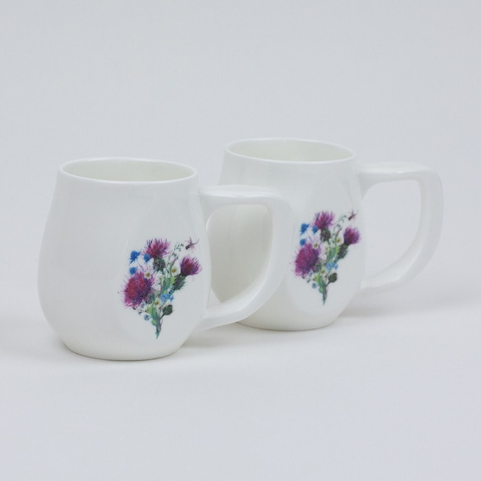 Two white fine bone china mugs with a colourful dragonfly printed on the side.